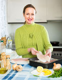 Happy woman cooking fish Royalty Free Stock Image
