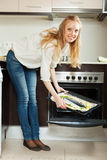 Happy woman cooking fish in oven Stock Photos
