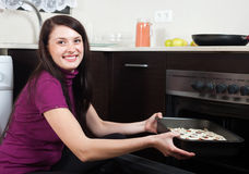 Happy woman cooking fish pie in the oven Stock Photography