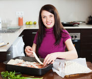 Happy woman cooking fish pie with raw salmon Stock Photos