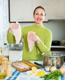 Happy woman cooking fish soup Royalty Free Stock Photos