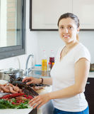Happy woman cooking marine products. In kitchen Royalty Free Stock Photo
