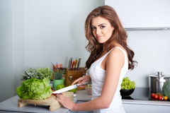 Happy woman cooking a meal in the kitchen Stock Photography