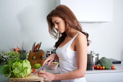 Happy woman cooking a meal in the kitchen Royalty Free Stock Images