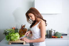 Happy woman cooking a meal in the kitchen Royalty Free Stock Image