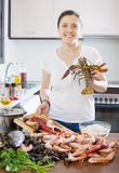 Happy woman cooking paella with seafood Royalty Free Stock Photos