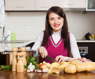 Happy woman cooking potatoes Stock Photos