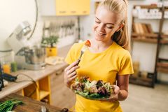 Happy woman cooking salad, bio food preparing. Happy woman cooking salad on the kitchen, healthy bio food preparing. Vegetarian diet, fresh vegetables and fruits Stock Image
