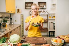 Happy woman cooking salad, bio food preparing. Happy woman cooking salad on the kitchen, healthy bio food preparing. Vegetarian diet, fresh vegetables and fruits Stock Photography