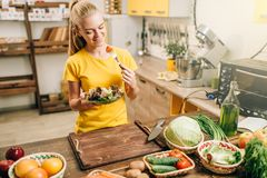Happy woman cooking salad, bio food preparing. Happy woman cooking salad on the kitchen, healthy bio food preparing. Vegetarian diet, fresh vegetables and fruits Stock Photos