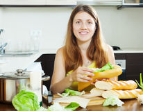 Happy woman cooking sandwiches with cheese and lettuce Stock Photos