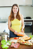 Happy woman cooking  sandwiches  with tomato Stock Photo