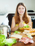 Happy woman cooking sandwiches Stock Photography
