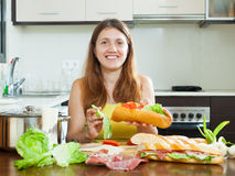 Happy woman cooking sandwiches Stock Photo