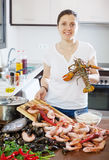 Happy woman cooking sea food specialties Stock Photography
