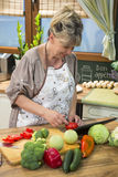 Happy woman cooking and using digital tablet in the kitchen. Royalty Free Stock Photos