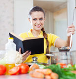 Woman cooking  vegetables with book Stock Photo
