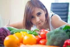 Happy woman cooking vegetables green salad Stock Images