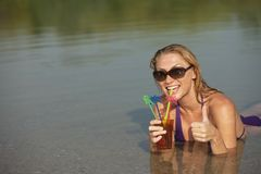 Happy woman with cool drink in the water Royalty Free Stock Images