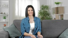 Happy woman on a couch talking at camera at home stock video