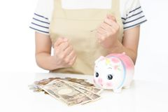 Piggy bank with money. Happy woman counting money at the table Stock Photos