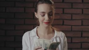 Happy woman counting money after winning in lottery on brick wall background stock video footage