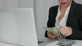 Happy Woman counts US dollars out of her laptop. Concept of abundance. Happy Businesswoman earns money on the Internet. Woman counts US dollars near her laptop Royalty Free Stock Photos