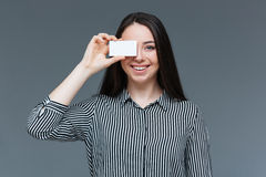 Happy woman covering eye with blank card Stock Photo