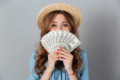 Happy woman covering face with money. Looking camera. Picture of excited young happy woman standing over grey wall wearing hat covering face with money. Looking stock photography