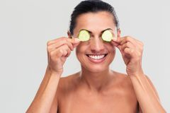 Happy woman covering her eyes with cucumber Royalty Free Stock Images