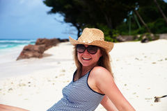 Happy woman in cowboy hat resting on a beach Royalty Free Stock Images