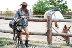 Happy woman cowgirl standing and holding saddle for riding horse. Happy beautiful young woman cowgirl in hat standing and holding saddle for riding horse Stock Images