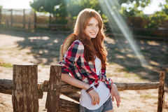 Happy woman cowgirl standing and relaxing on ranch Stock Photo
