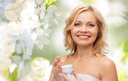 Happy woman with cream jar Stock Photos