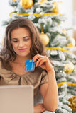Happy woman with credit card and laptop near christmas tree Stock Images