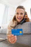 Happy woman with credit card laying on sofa and talking phone Royalty Free Stock Image