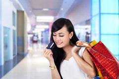 Happy woman with credit card and shopping bags. Asian woman looking at her credit card while carrying shopping bags Stock Photos