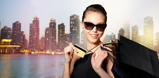 Happy woman with credit card and shopping bags Stock Images