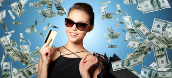 Happy woman with credit card and shopping bags. Sale, finances, people and luxury concept - happy beautiful young woman in black sunglasses with credit card and Royalty Free Stock Image