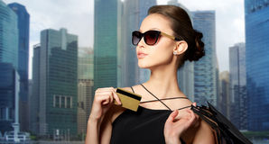 Happy woman with credit card and shopping bags. Sale, finances, people and luxury concept - happy beautiful young woman in black sunglasses with credit card and Stock Images