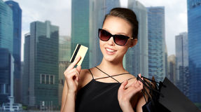 Happy woman with credit card and shopping bags. Sale, finances, people and luxury concept - happy beautiful young woman in black sunglasses with credit card and Stock Image