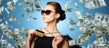 Happy woman with credit card and shopping bags. Sale, finances, people and luxury concept - happy beautiful young woman in black sunglasses with credit card and Royalty Free Stock Photos
