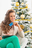 Happy woman with credit card and tablet pc near christmas tree Stock Photo