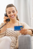 Happy woman with credit card talking phone while sitting on sofa Royalty Free Stock Photo