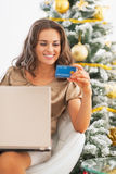 Happy woman with credit card using laptop near christmas tree Royalty Free Stock Images
