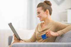 Happy woman with credit card using tablet pc Stock Images