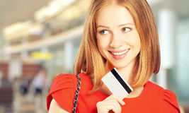 Happy woman with a credit card went on shopping Royalty Free Stock Photography