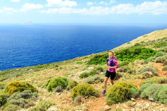 Happy woman cross country running in beautiful mountains Stock Photos