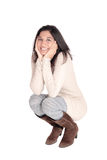 Happy woman crouching on floor. A beautiful young Hispanic woman in a knitted dress and brown boots Royalty Free Stock Image