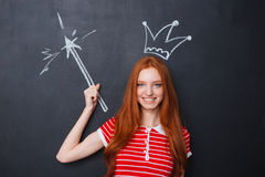 Happy woman with crown and magic drawn on blackboard background Royalty Free Stock Photography